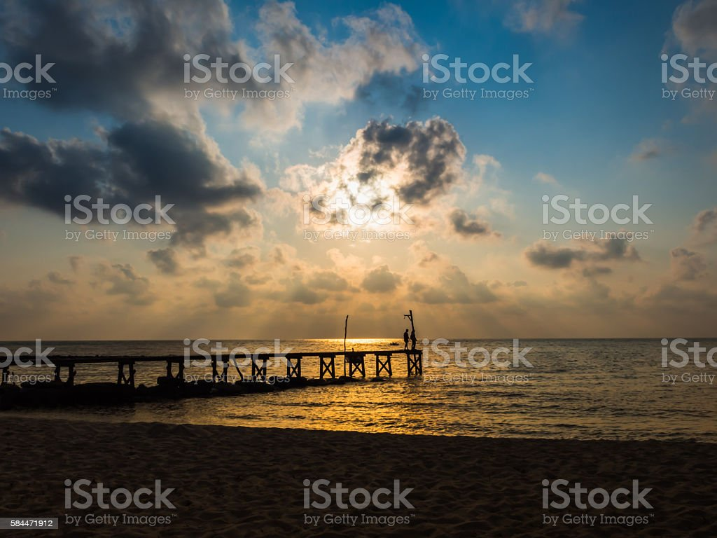 Wooded bridge to the sea between sunset stock photo