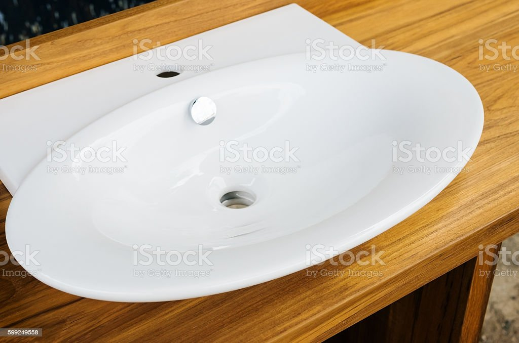 Wooden a pedestal with porcelain washbasin stock photo