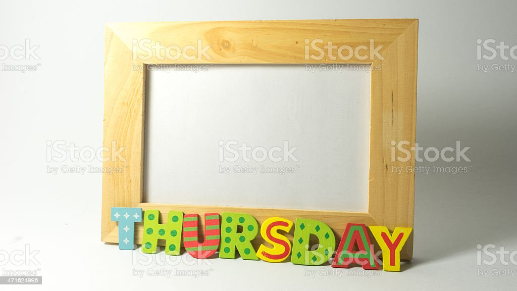 Wooden alphabet letter forming daily word on empty photo frame stock photo