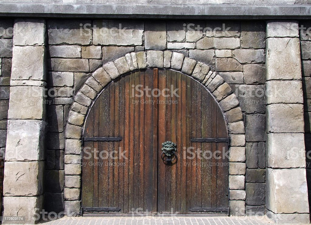 Wooden arched doors surrounded by stones in medieval design stock photo