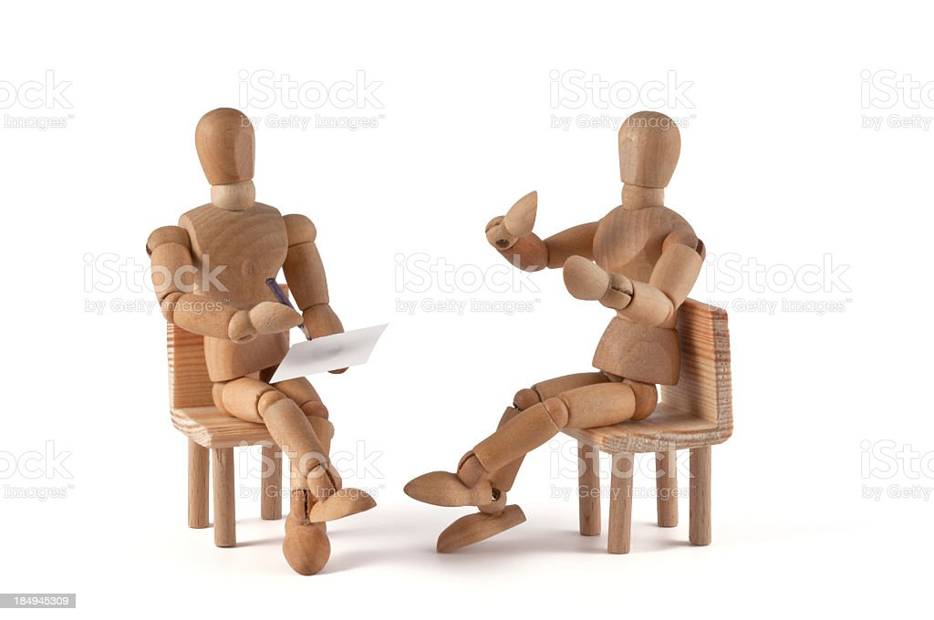 Wooden art mannequins set up as if they were talking stock photo