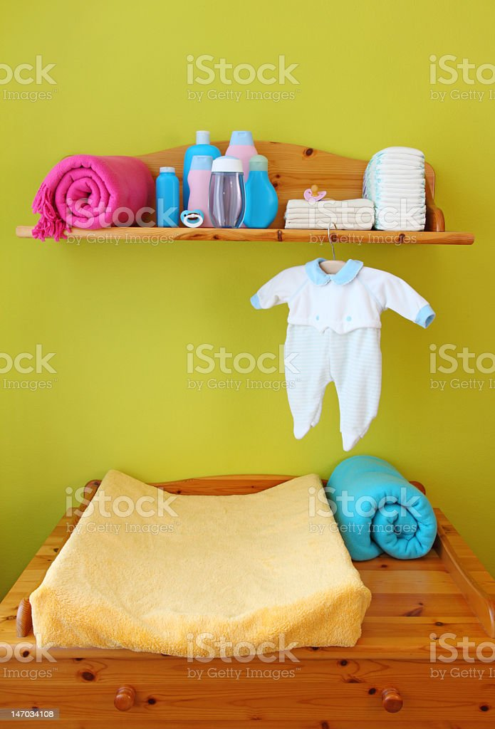 Wooden baby changing table with changing pad and necessities stock photo