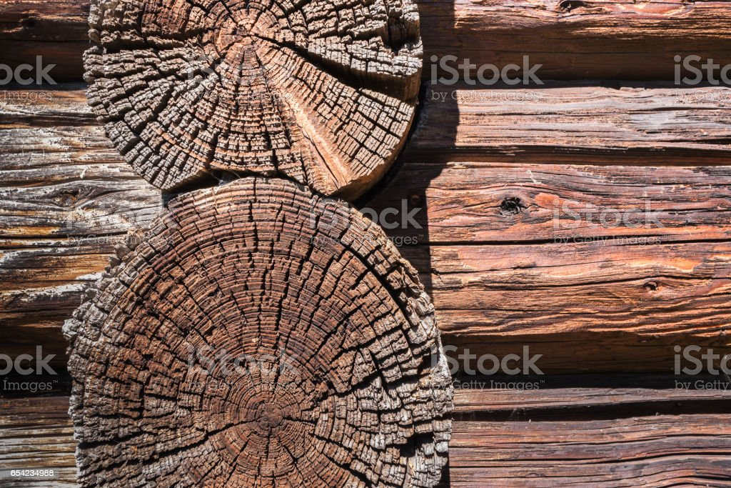 Wooden background. Close-up wall of old dilapidated longitudinal and transverse logs. stock photo