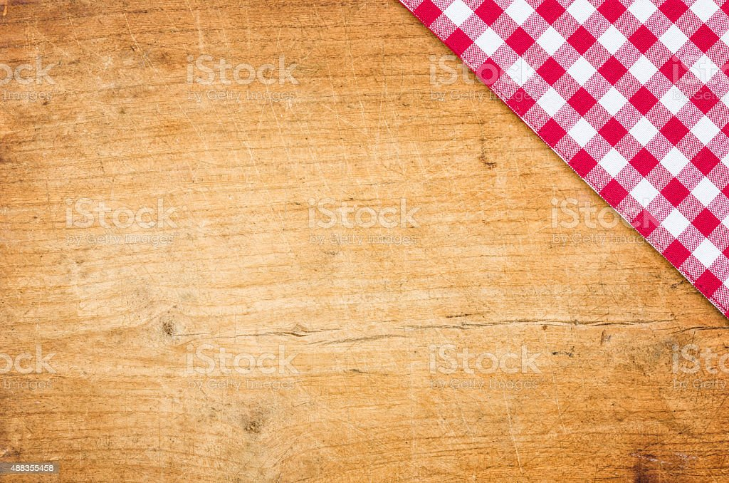 Wooden background with a checkered tablecloth stock photo