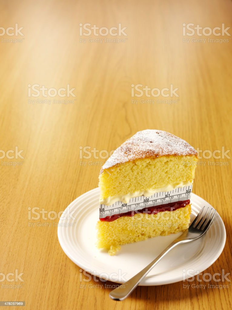 Wooden Background with a Sponge Cake and Tape Measure stock photo