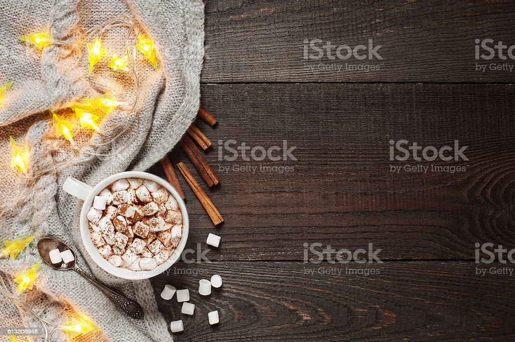 Wooden background with cup of cacao, marshmallow and garland stock photo