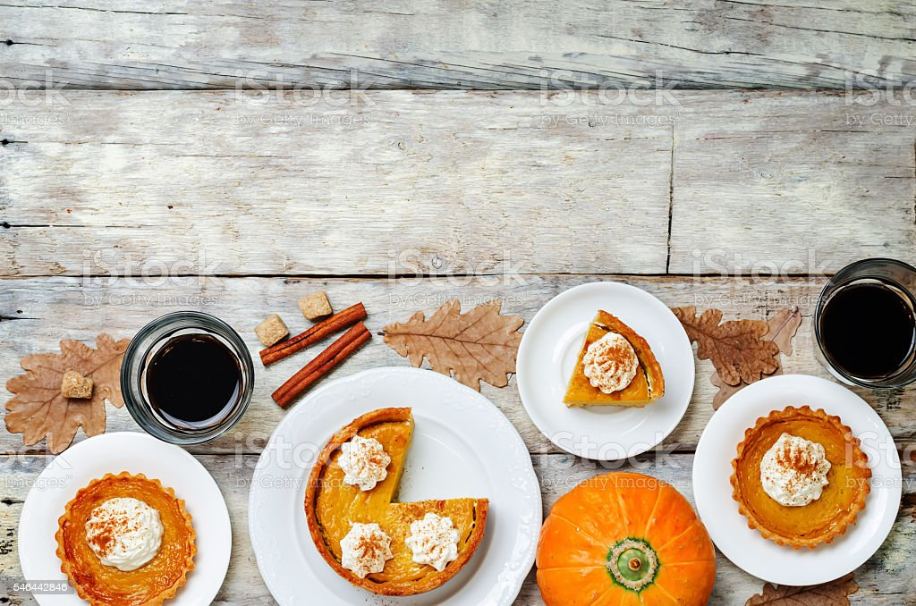 wooden background with pumpkin pies, pumpkin and coffee. Autumn concept stock photo