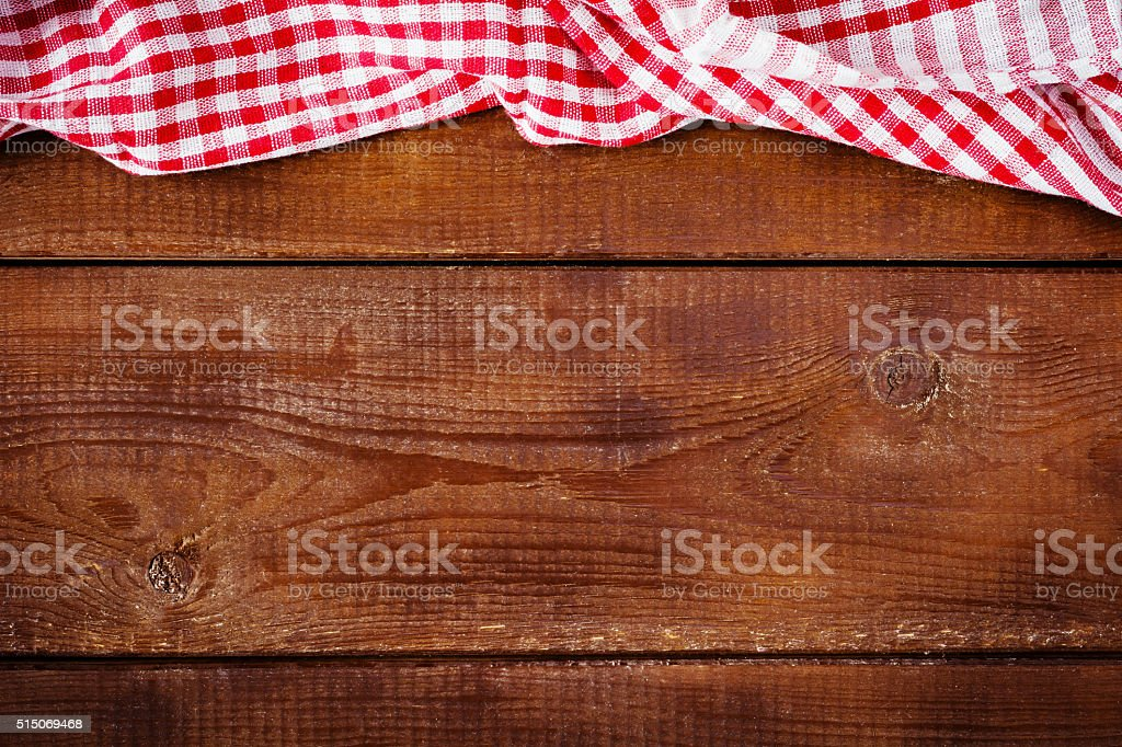 Wooden background with red and white plaid napkin stock photo