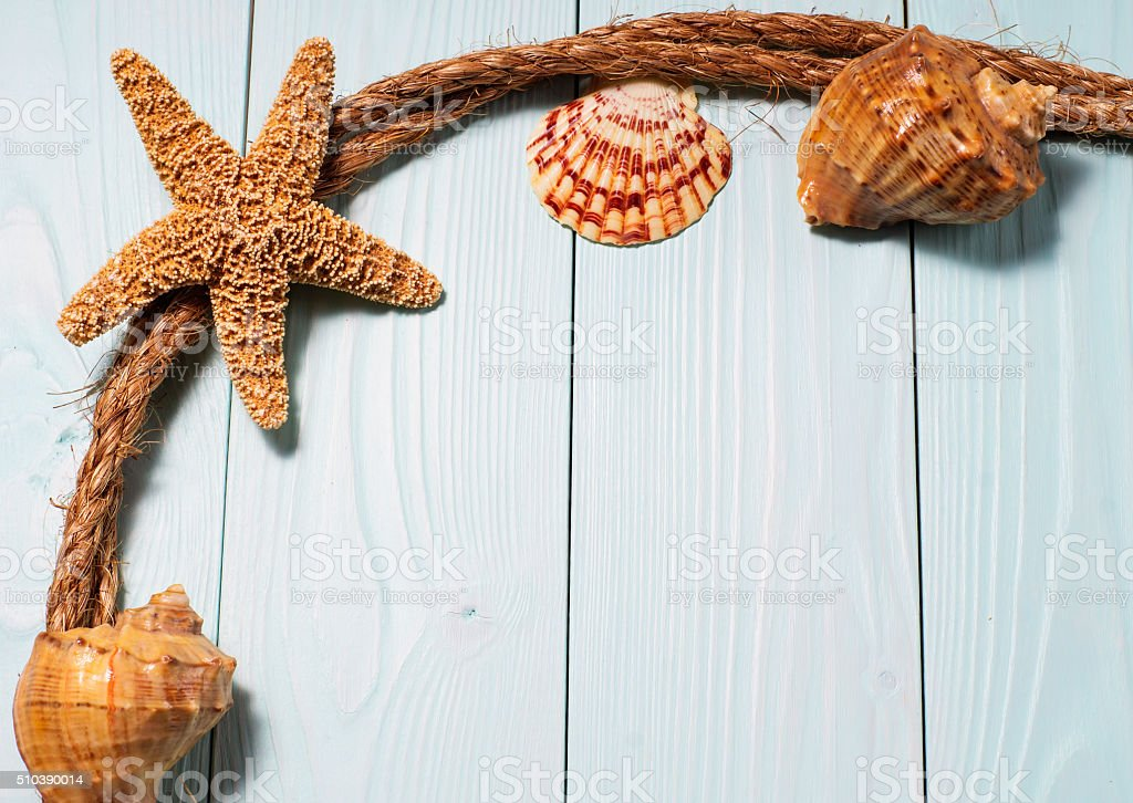 Wooden background with starfish, sea shells and marine rope stock photo