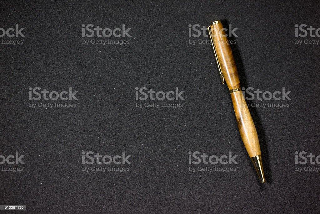 Wooden ballpen on black stock photo