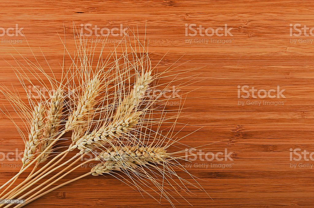 Wooden bamboo cutting board with nine wheat ears royalty-free stock photo