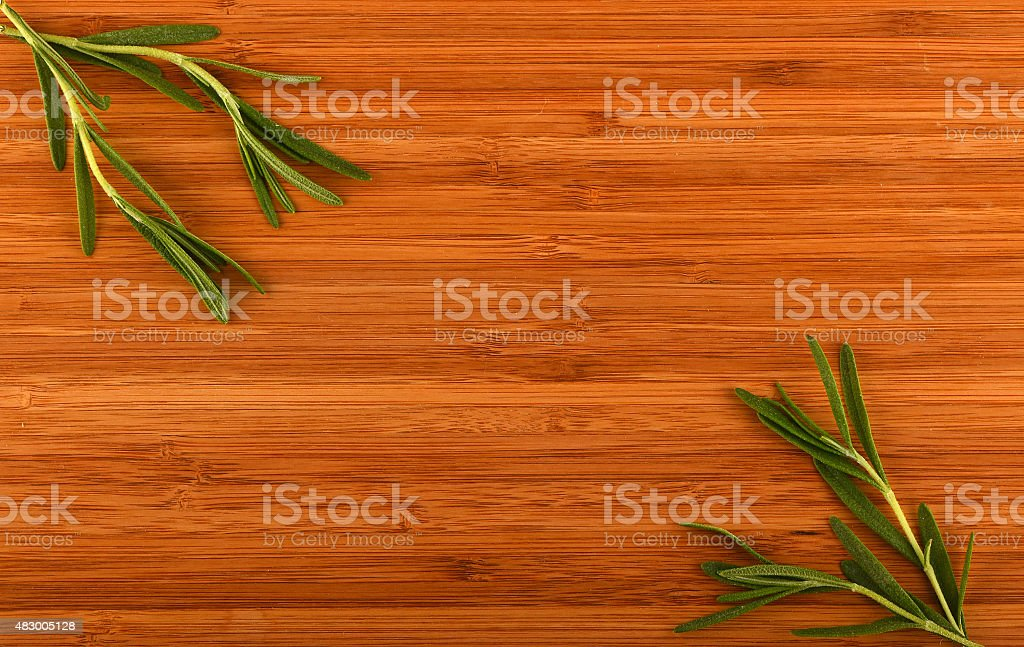 Wooden bamboo cutting board with rosemary leaves royalty-free stock photo