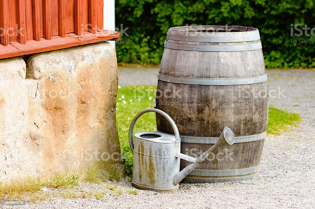 Wooden barrel and watering can stock photo