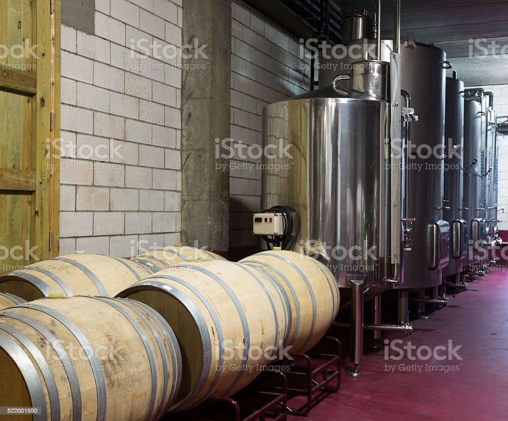 Wooden barrels and stainless tanks with processing wine stock photo