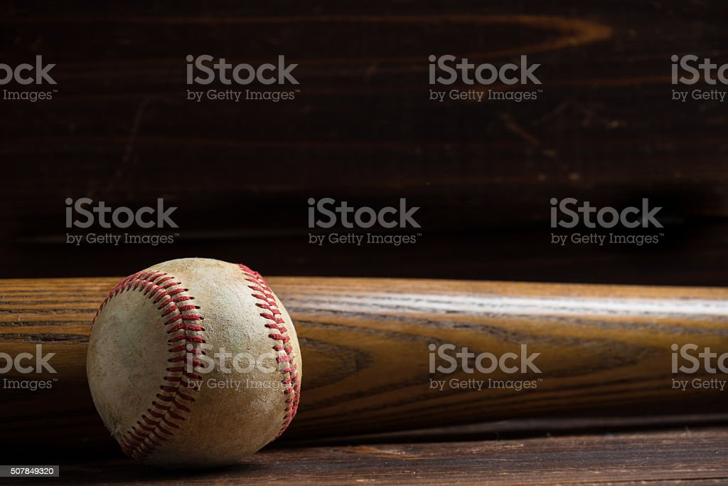 Wooden baseball bat and ball on a wood background stock photo
