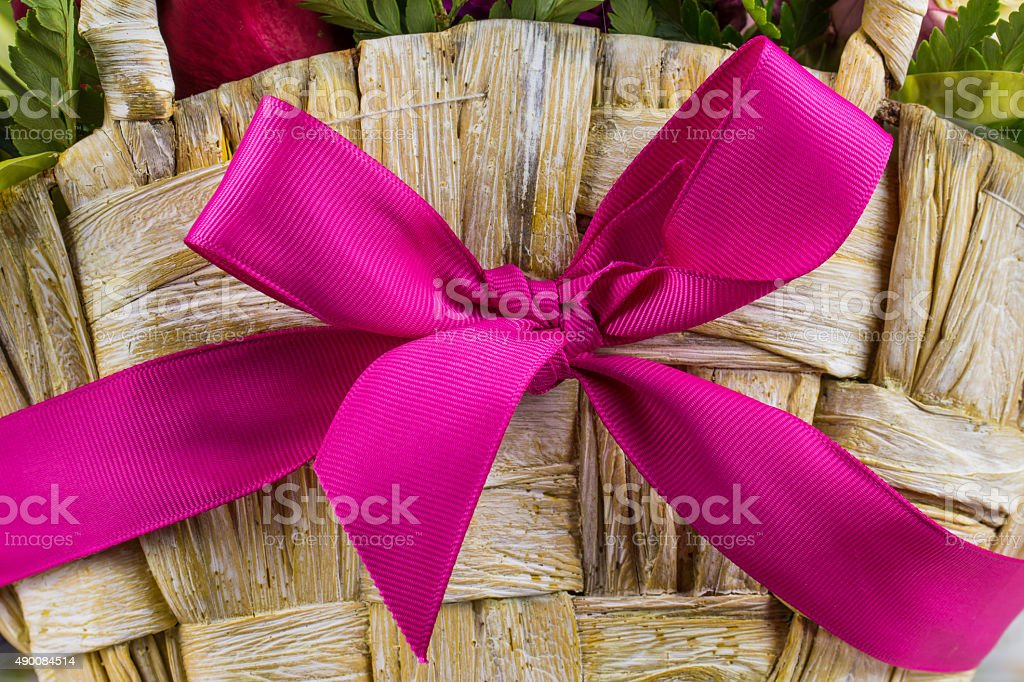 Wooden basket with pink ribbon and flowers stock photo