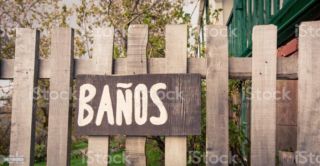 wooden bathroom sign in Spanish stock photo