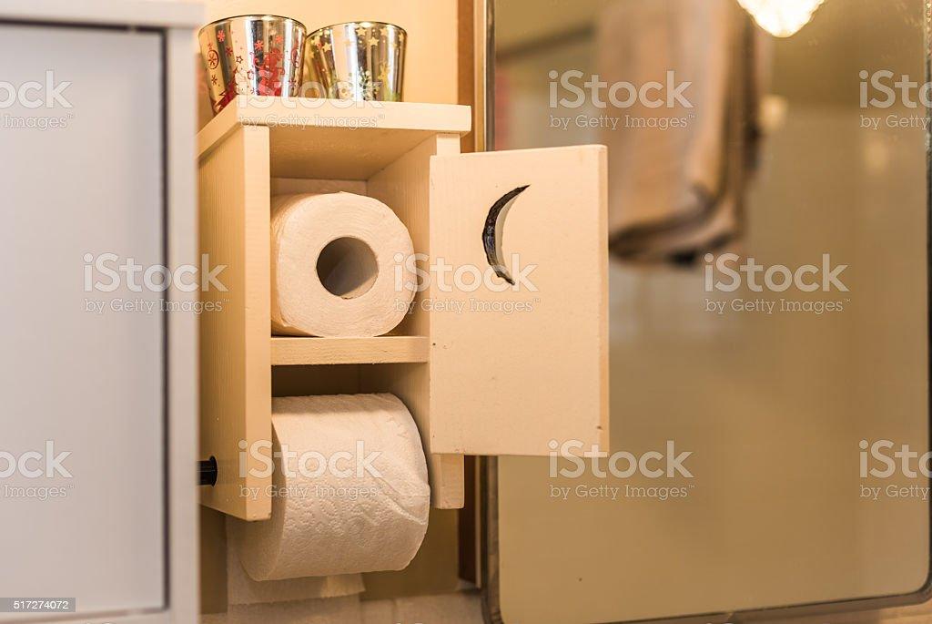 Wooden bathroom toilet paper holder with crescent moon door. stock photo