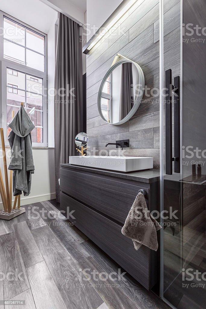 Wooden bathroom with round mirror stock photo