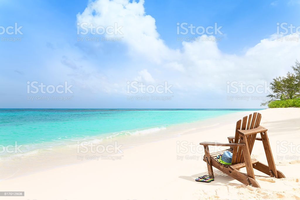 Wooden beach chair with hat and slippers at tropical beach stock photo