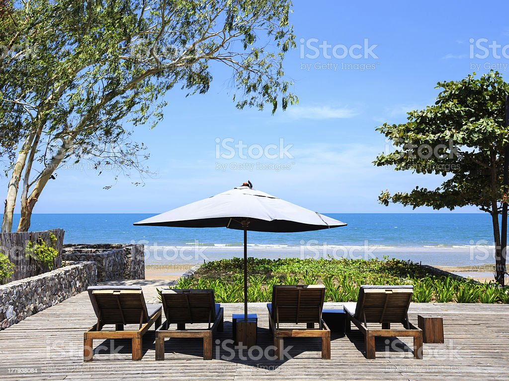 Wooden beach chairs with sun umbrella royalty-free stock photo