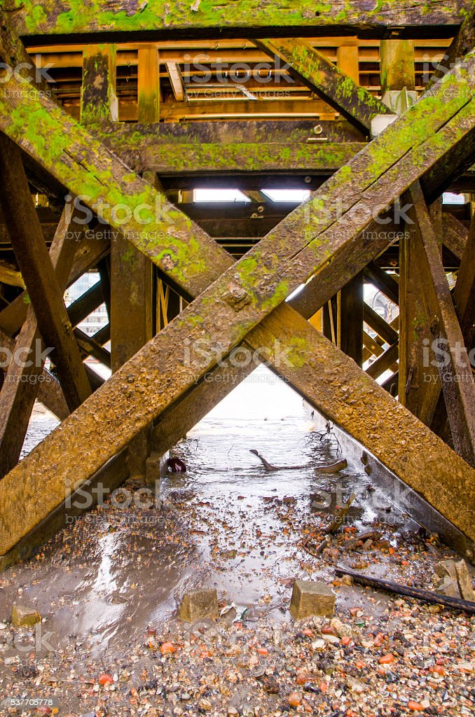 Wooden beam structure under pier on Thames River stock photo