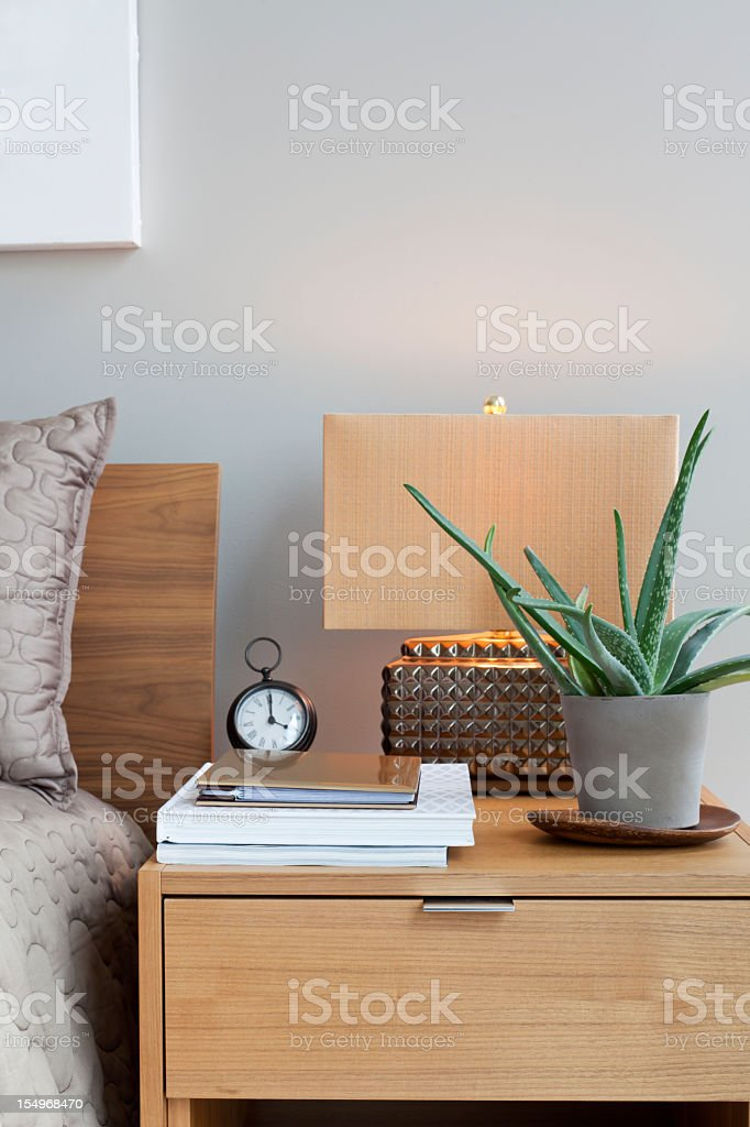 Wooden bedside table with a lamp, plant, clock, and papers stock photo