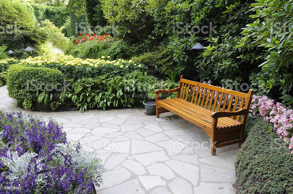 Wooden bench in a corner of lush garden royalty-free stock photo