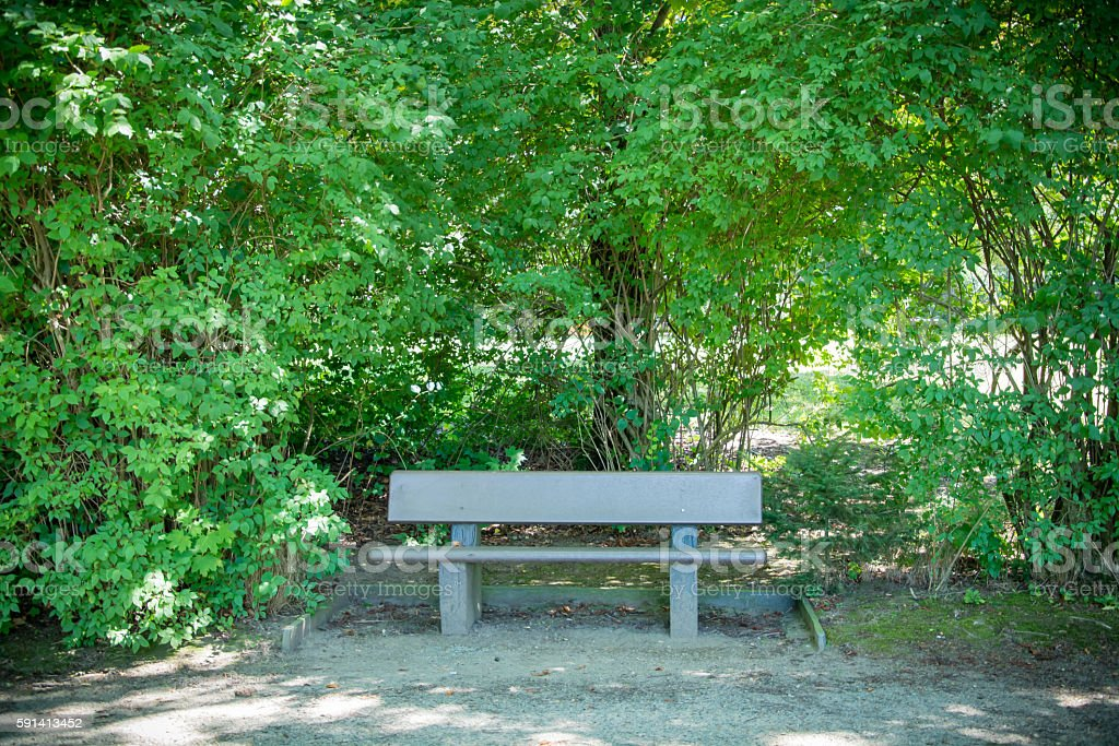 Wooden bench in city park stock photo