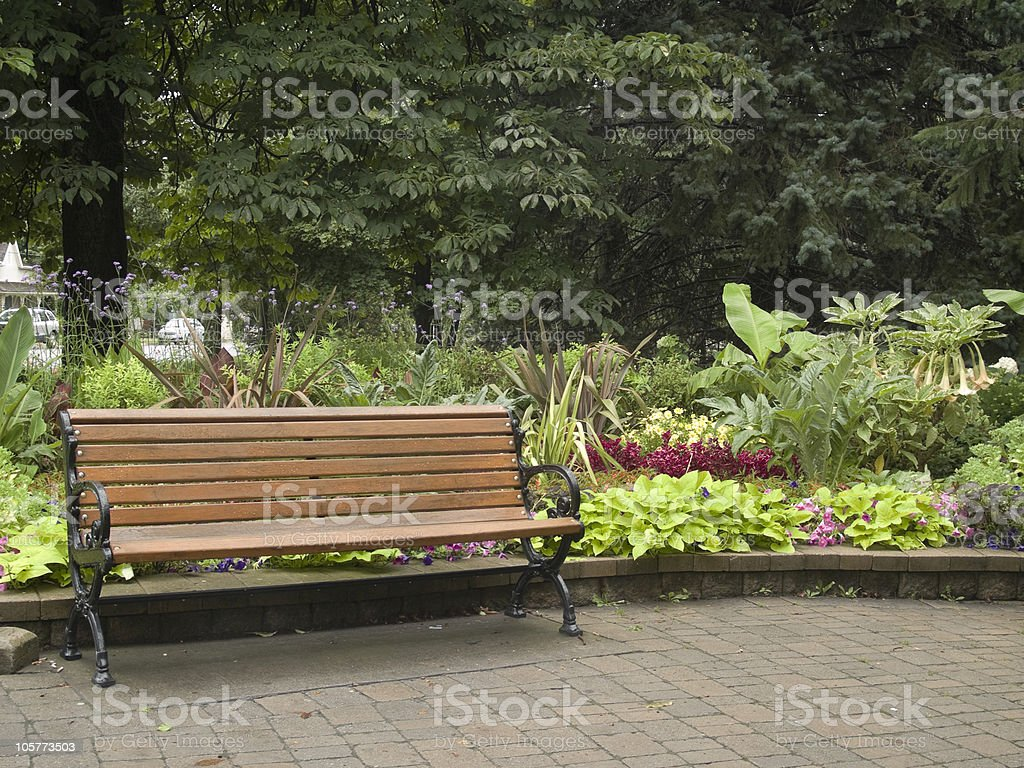 Wooden bench in front of flower bed in small park royalty-free stock photo