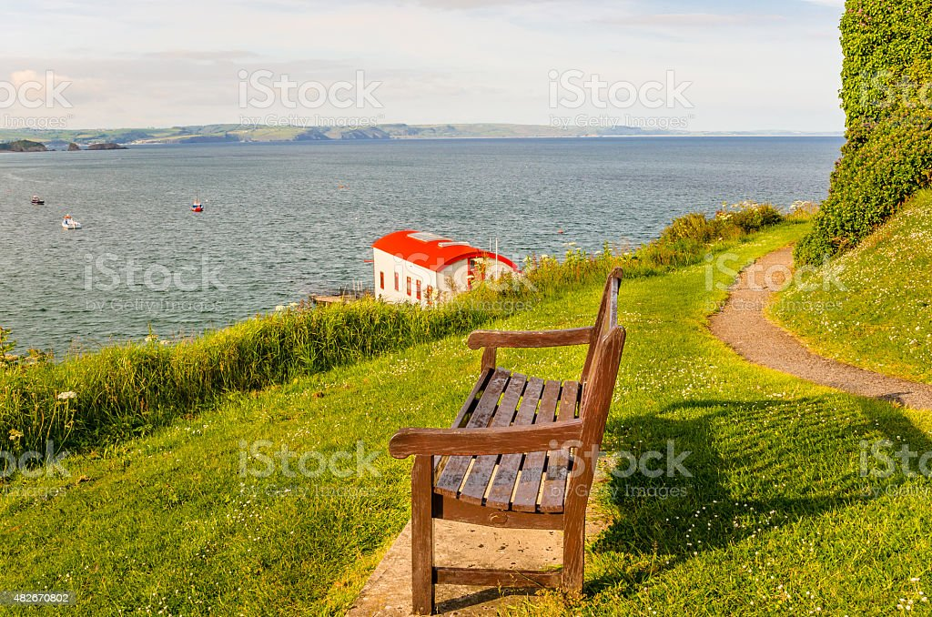 Wooden Bench in Front of the Sea at Sunset stock photo