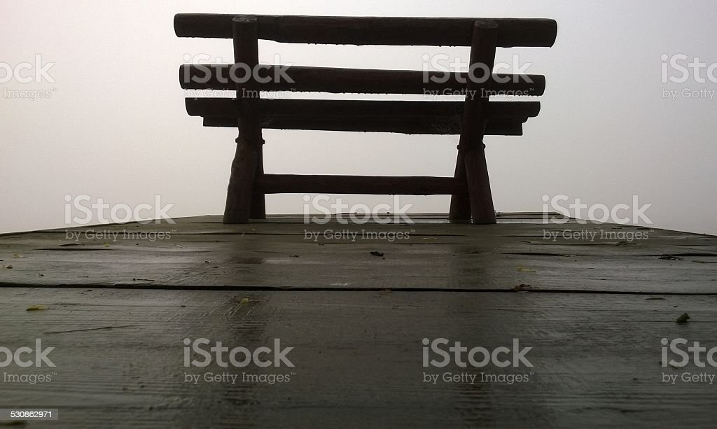 Wooden bench in the mist royalty-free stock photo
