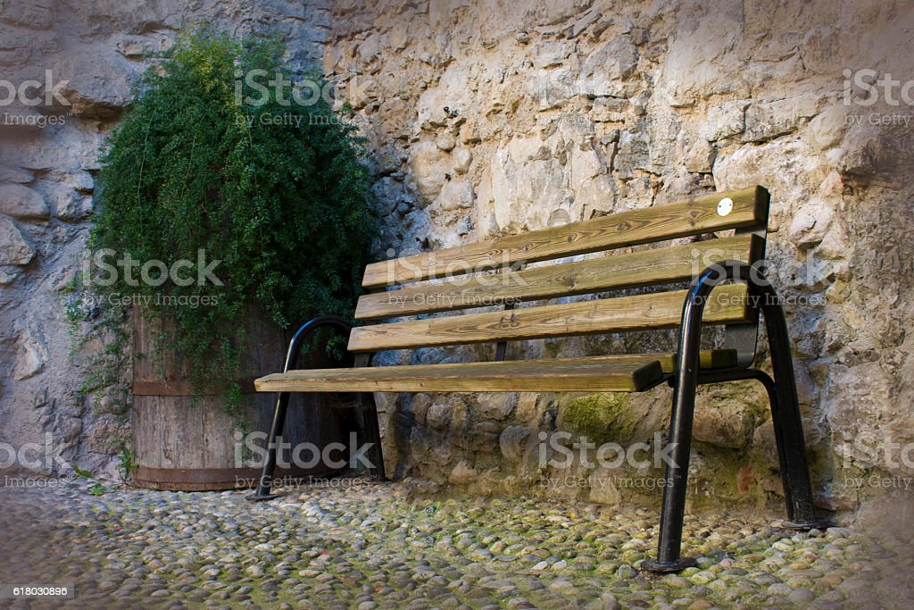 wooden bench near a stone wall stock photo