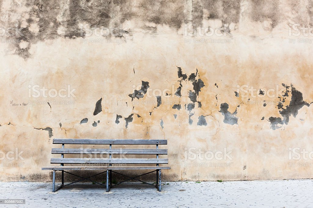 Wooden bench next to old church wall. stock photo