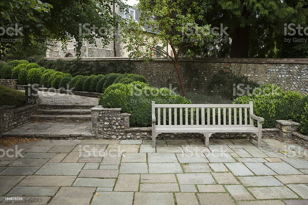 Wooden bench on old stone patio stock photo