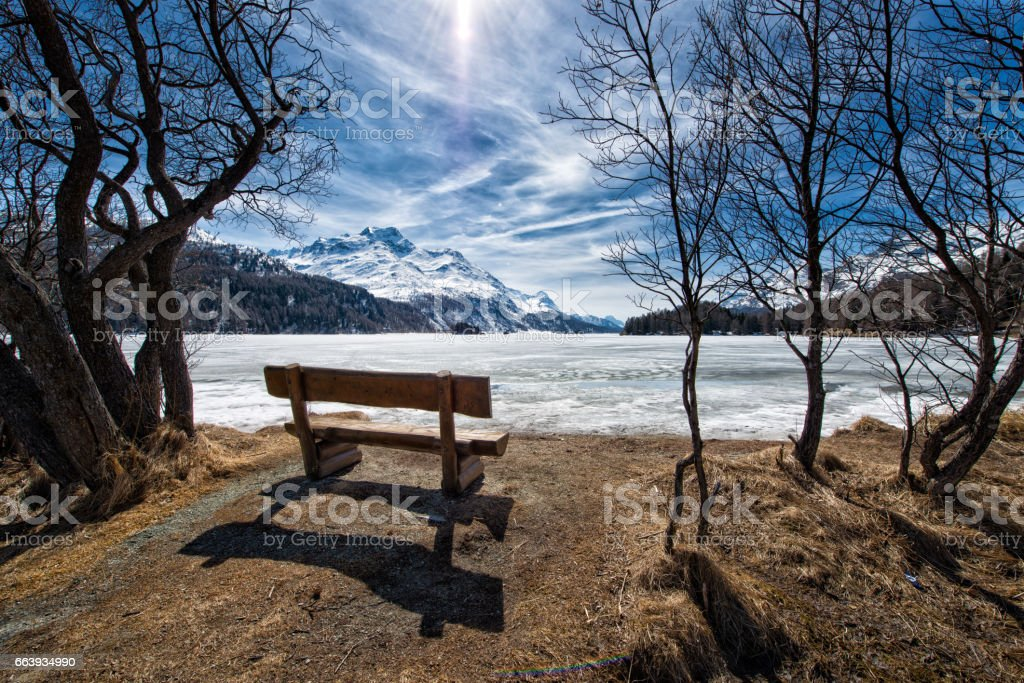 Wooden bench to admire the scenery on an alpine lake ice stock photo