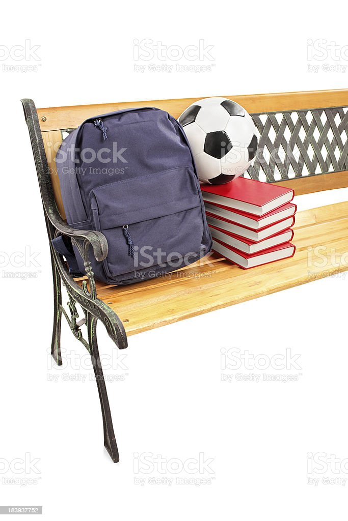 Wooden bench with books, school bag and football on it royalty-free stock photo