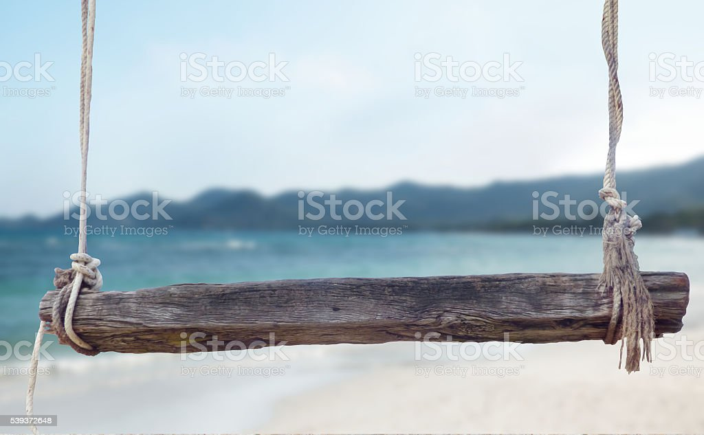 wooden bench with ropes front of blurred beach photo stock photo