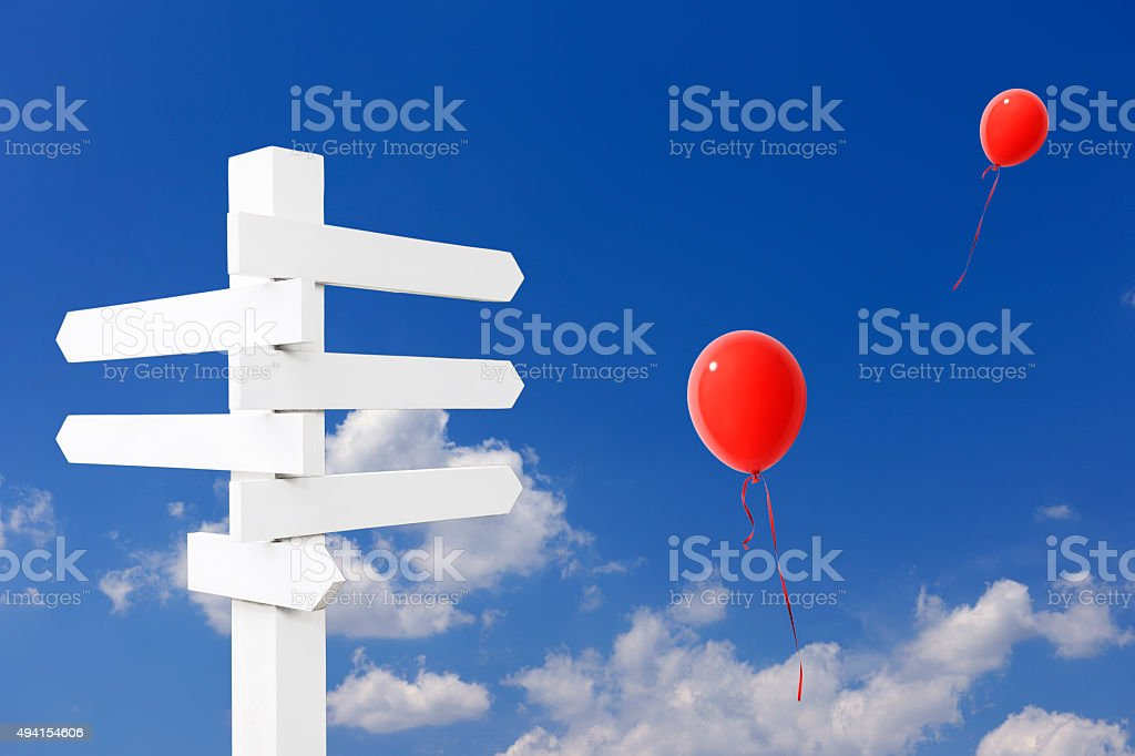Wooden blank road sign with red balloons against clear sky stock photo