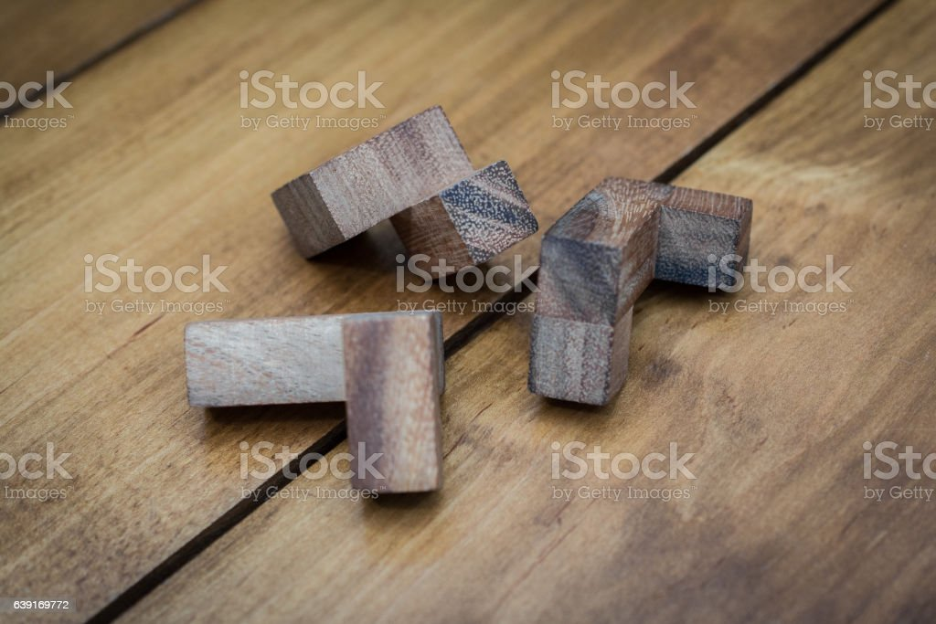 Wooden Block Brain Teaser on Wood Background Pieces Close Up stock photo