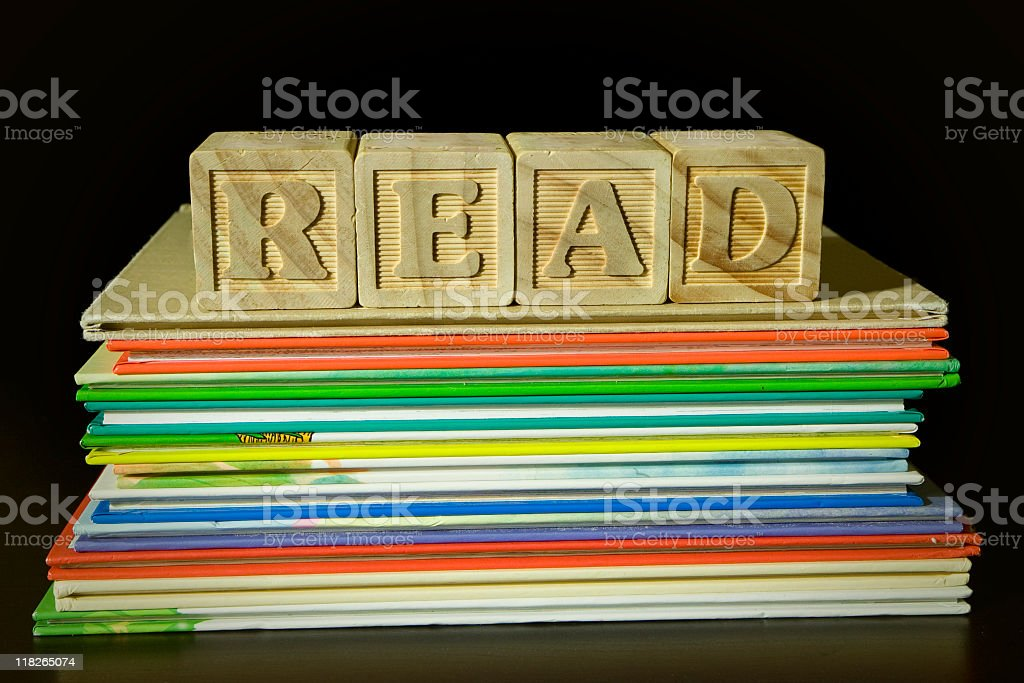 Wooden blocks spelling READ on top of pile of books stock photo