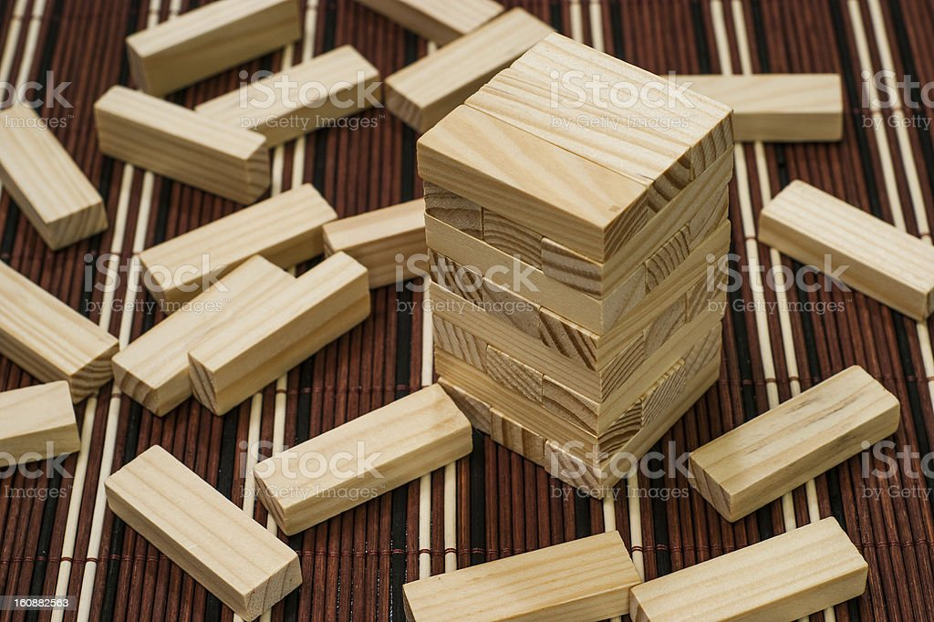 Wooden blocks tower and block spread around royalty-free stock photo