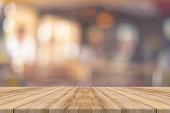 Wooden board empty table blur in coffee shop.