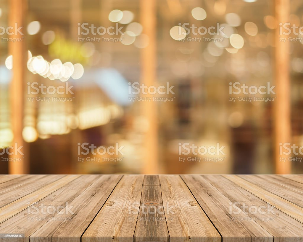 Wooden board empty table blurred in coffee shop background. stock photo