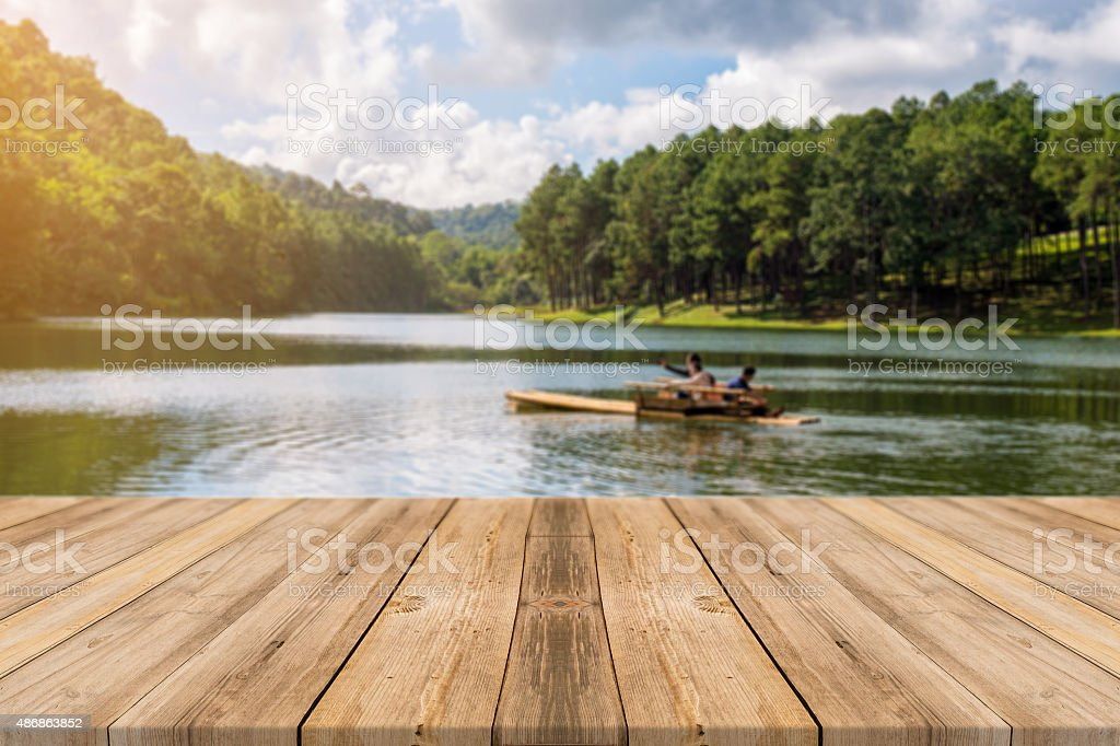 Wooden board empty table blurred lake in fores background. stock photo
