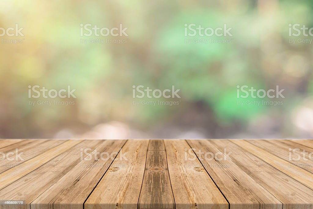 Wooden board empty table blurred trees in forest background. stock photo