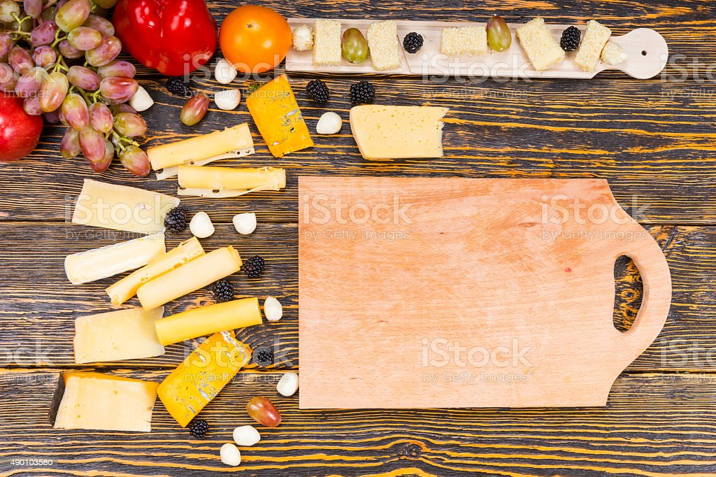 Wooden Board Surrounded by Cheese and Fresh Fruit stock photo
