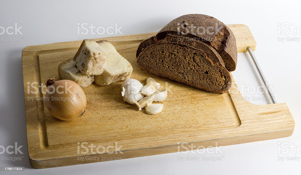 Wooden board with bread, lard, garlic and onion royalty-free stock photo