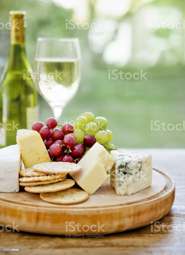 Wooden board with cheese, grapes and wine in the background stock photo