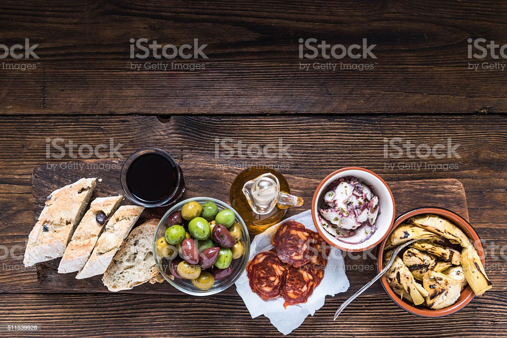 Wooden board with tapas, olives and salami and olive oil stock photo